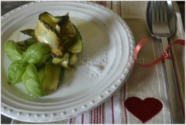 Présentation des tagliatelles de la plancha courgettes bio servies dans une assiette blanche avec une feuille de basilic