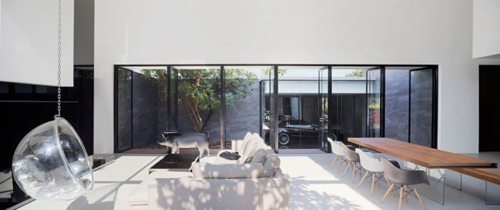 Living and dining area lit with light drawn from internal courtyard space