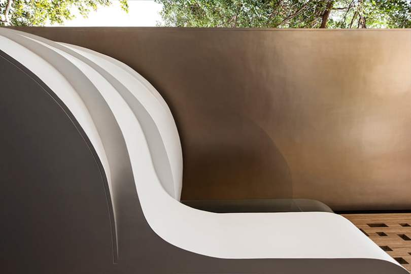 a bold sculptural feature elevated above the ground in front elevation design of indian house