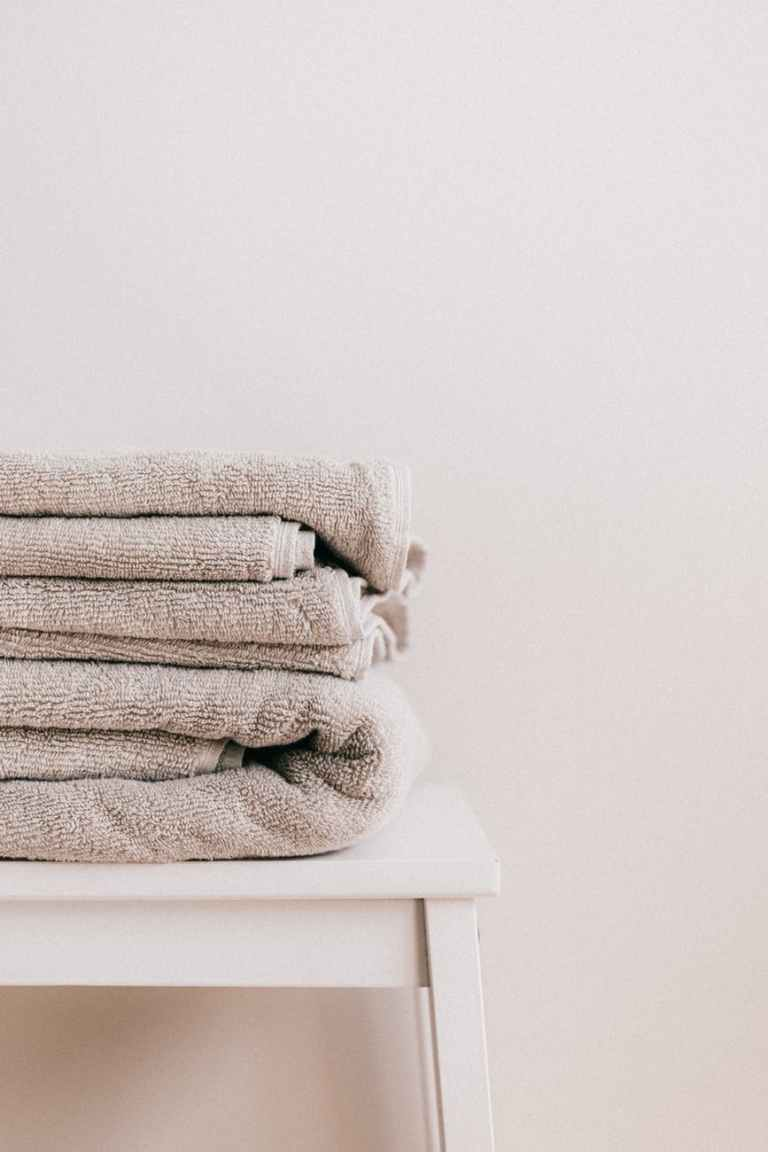 stack of clean towels on white stool