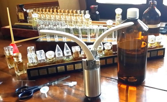 AbdesSalaam's crimper on a table with perfume alcohol, empty bottles, and a number of his own finalized scents in mini sizes. Photo: my own.