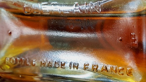 Bottom of my extrait bottle, with the squiggly symbol to the far right. Photo: my own.