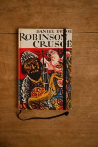 """Van het kinderboek """" Robinson Crusoë door Daniel Defoe"""" hebben we een notitieboekje gemaakt. Blanco pagina's, voorzien van een zwart elastiek en een lintje."""