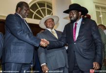 Le président du Soudan du Sud, Salva Kiir (à droite) serre la main au chef rebelle Riek Machar durant les pourparlers de paix à Entebbe, en Ouganda, sous l'oeil du président ougandais Yoweri Museveni (centre), le 7 juillet 2018. | AFP | SUMY SADURNI
