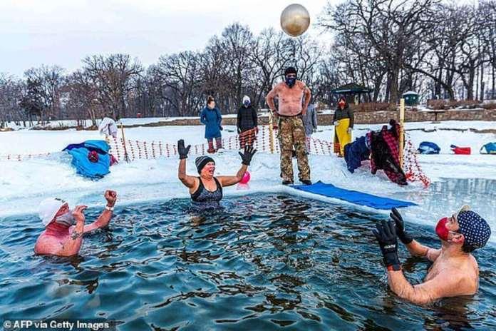 Les membres du groupe des `` submergents '' jouent alors qu'ils plongent dans une piscine à 37,4 degrés F creusée dans la glace du lac Harriet, au Minnesota, samedi.