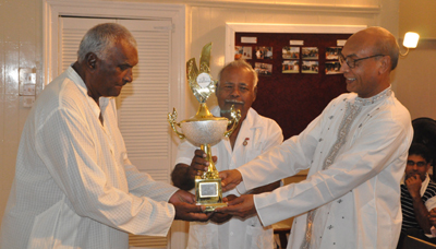 Mr Misri Persaud of the Guyana Hindu Prachaar Sabha, left, collects the award on behalf of Randall Butisingh from Indian High Commissioner to Guyana Sabeet Kumar Mandal.