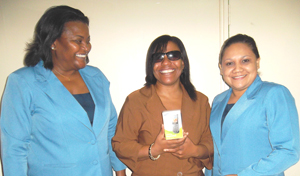 A smiling Stacey Greaves (at centre) displays her new cellular phone. She is flanked by the GT&T Public Relations team of Allison Parker (left) and Nadia DeAbreu.