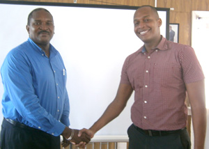 Former President Clinton Urling (right) shakes hands with the new President of the GCCI, Lance Hinds