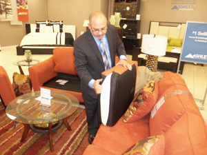 Ashley's International Marketing Specialist, Jesus Dacal, explaining the special aspects of Ashley furnishing while showing invitees the superior quality of the product.