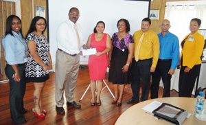 GCCI President Lance Hinds hands over the financial donation to Dr Paloma Mohamed-Martin. They are flanked by representatives of private sector companies.