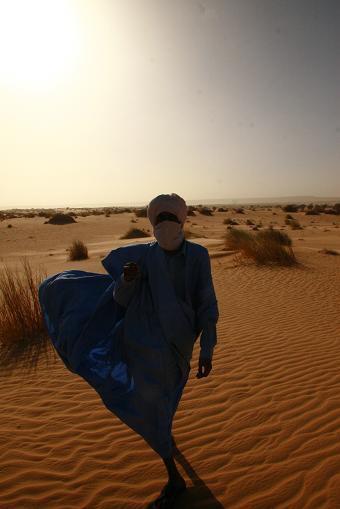 遊牧民の伝統衣装を纏った友達ムラーイ。足元に広がる砂紋が美しい
