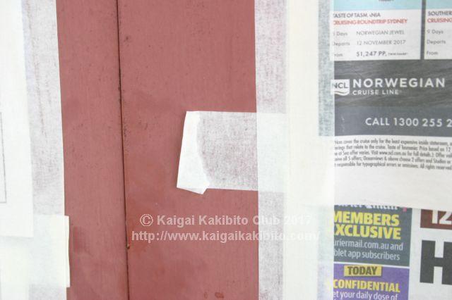 新聞紙を貼ったガラスドア