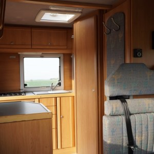 Zwischen Sitzbank und Küche befindet sich ein großer Schrank und die Nasszelle