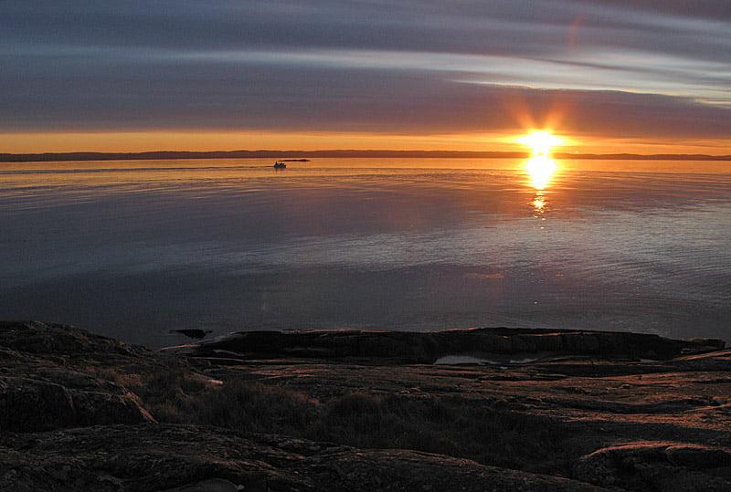 Soluppgång, en fiskebåt på väg söderut