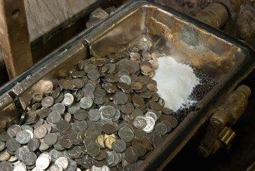 dirty coins being washed in a drum