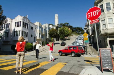 Visitors are posing for a photo with Coit Tower