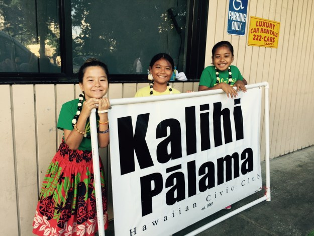 Kids holding Kalihi Palama Hawaiian Civic Club banner.