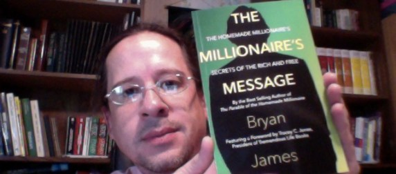 "Publisher Tony Michalski poses with Bryan James's new book ""The Millionaire's Message: The Homemade Millionaire's Secrets of the Rich and Free."""