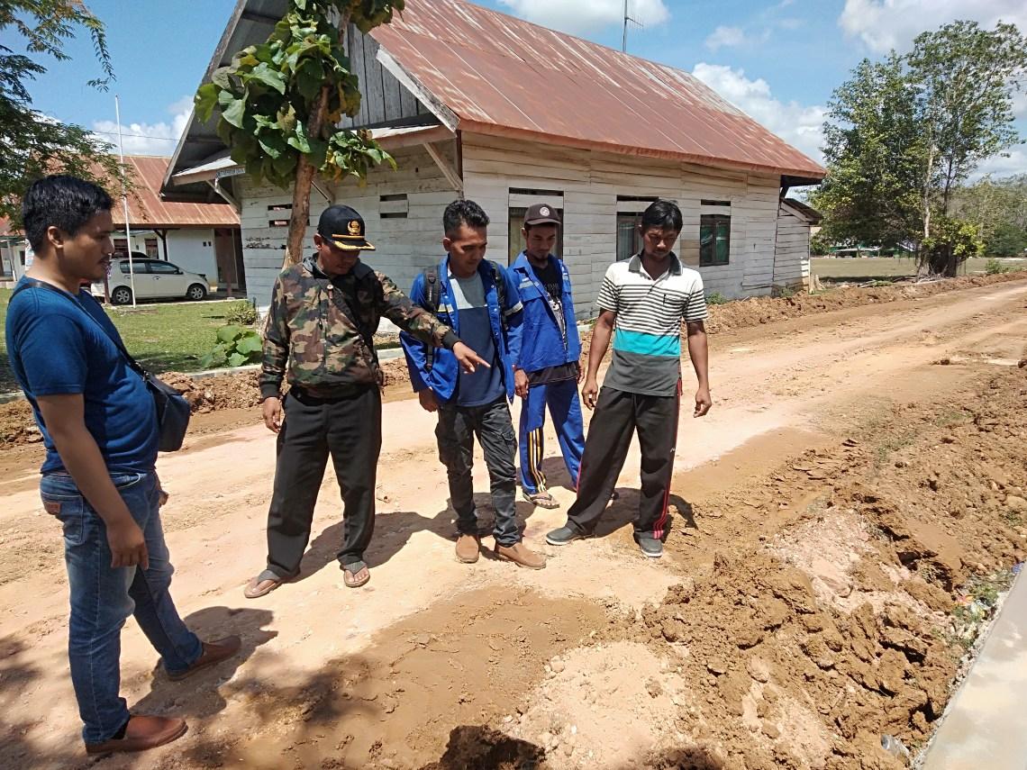 Ketgam : Pj Kades Wawonggura Alamsyah polingai saat memantau pengerjaan Peningkatan jalan bersama TPK Nur Kholis Dan Bendahara Desa Nurwahyudin.
