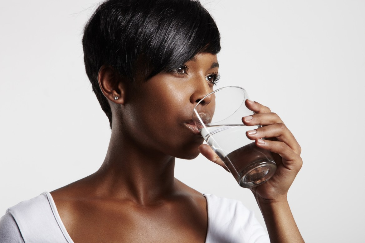 black woman in white t-shirt drinking water