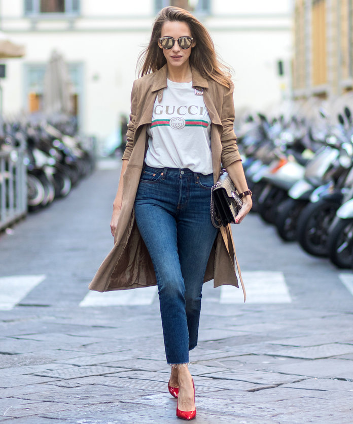 FLORENCE, ITALY - JANUARY 11: German fashion blogger and model Alexandra Lapp is wearing retro vibe Gucci printed cotton T-shirt, featuring a throwback Gucci logo, this piece features distressed detailing around the neckline, slim fit Wedgie Icon Fit Jeans from Leviâs, suede /buckskin leather trench coat from Oui, Dionysus GG Supreme Medium Gucci shoulder bag, Le Specs sunglasses, red pumps from Gianvito Rossi on January 11, 2017 in Florence, Italy. (Photo by Christian Vierig/Getty Images)