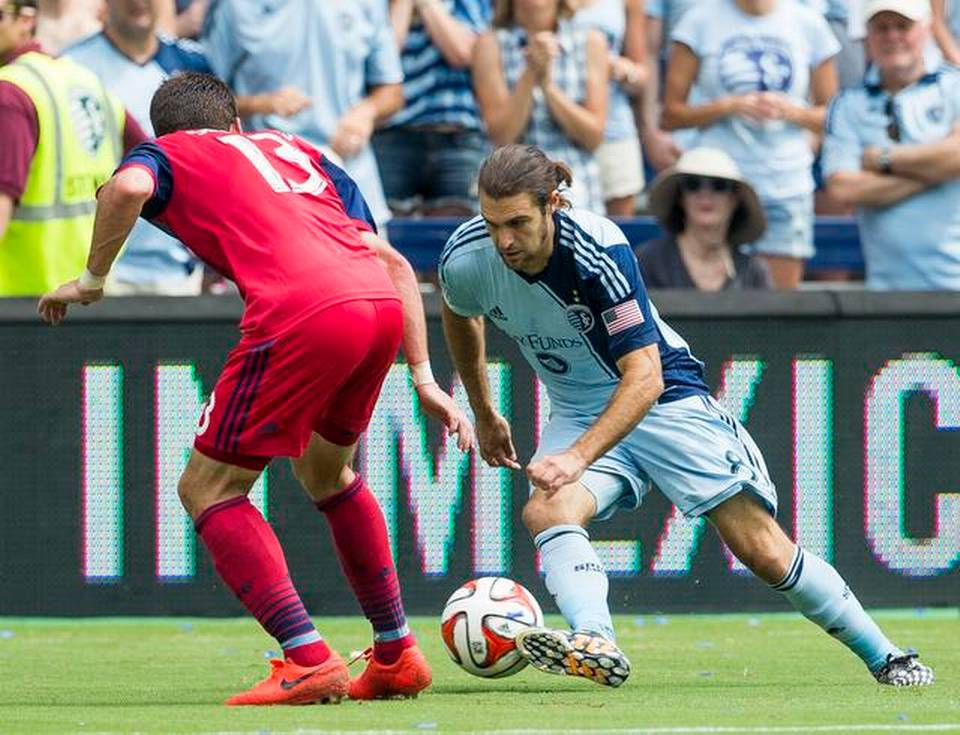Graham Zusi (8) of Sporting Kansas City controls the ball against Gonzalo Segares (13) of the Chicago Fire in Kansas City, Kansas, at Sporting Park on Sunday, July 6, 2014.