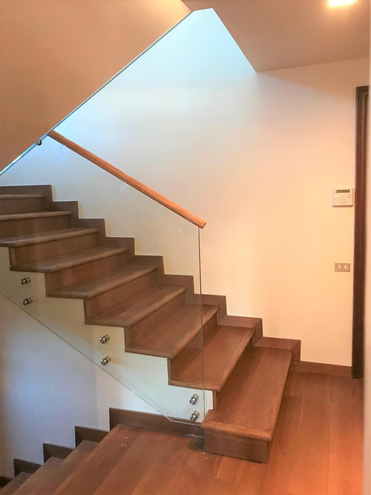 Treppengelaender in Glas mit aufgesetztem Holzhandlauf