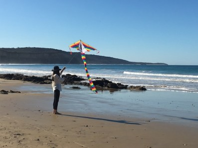 Girl on beach flying kite in Anglesea Great Ocean Road