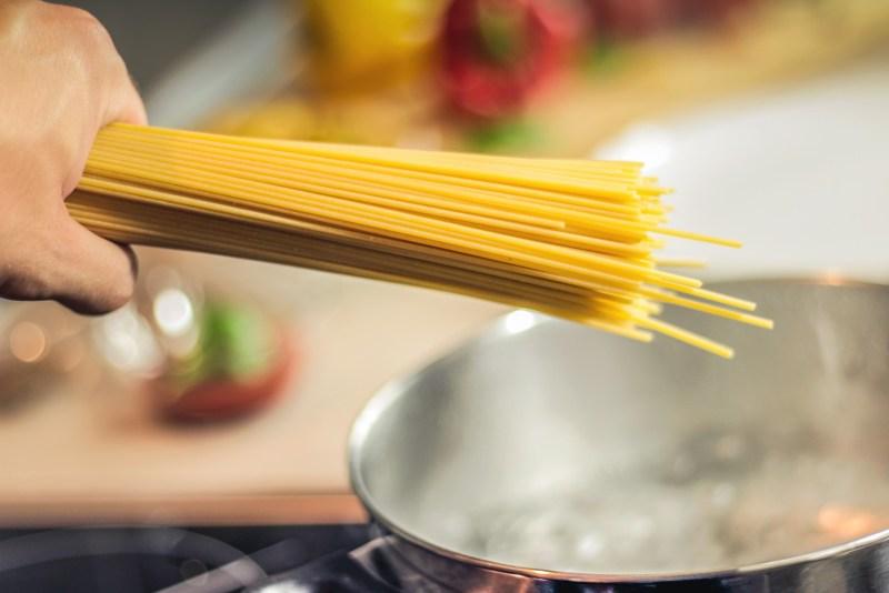 Una manciata di spaghetti che sta per essere tuffata in una pentola di acqua in ebollizione