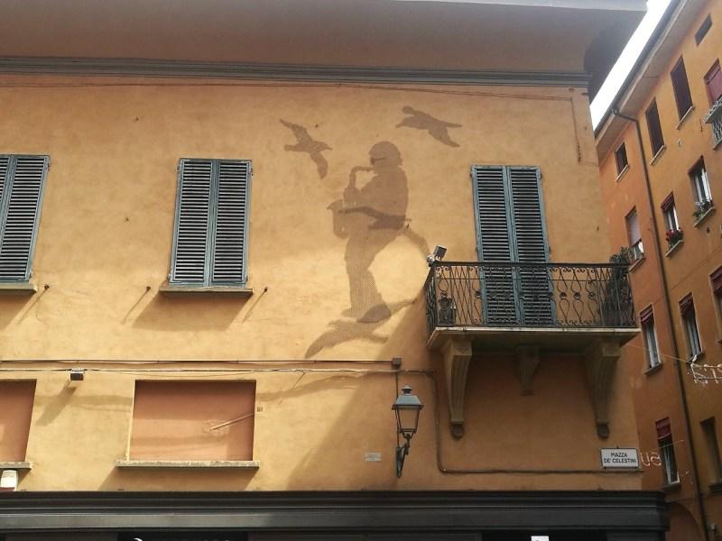 Il disegno di rete metallica dedicato a Dalla a Piazza de' Celestini ritrae il maestro mentre suona il sax fra le rondini.