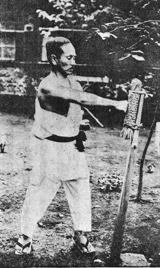 Funakoshi Gichin, the originator of Shotokan, posing with a makiwara