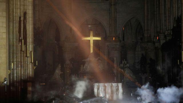 Juste après l'incendie de Notre-Dame, dans la nef toujours envahie de fumée, un rayon de soleil illumine la grande croix dorée.