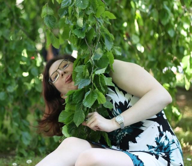 Photo d'une jeune fille en robe à moitié cachée derrière une branche de saule pleureur et tirant la langue à la photographe.