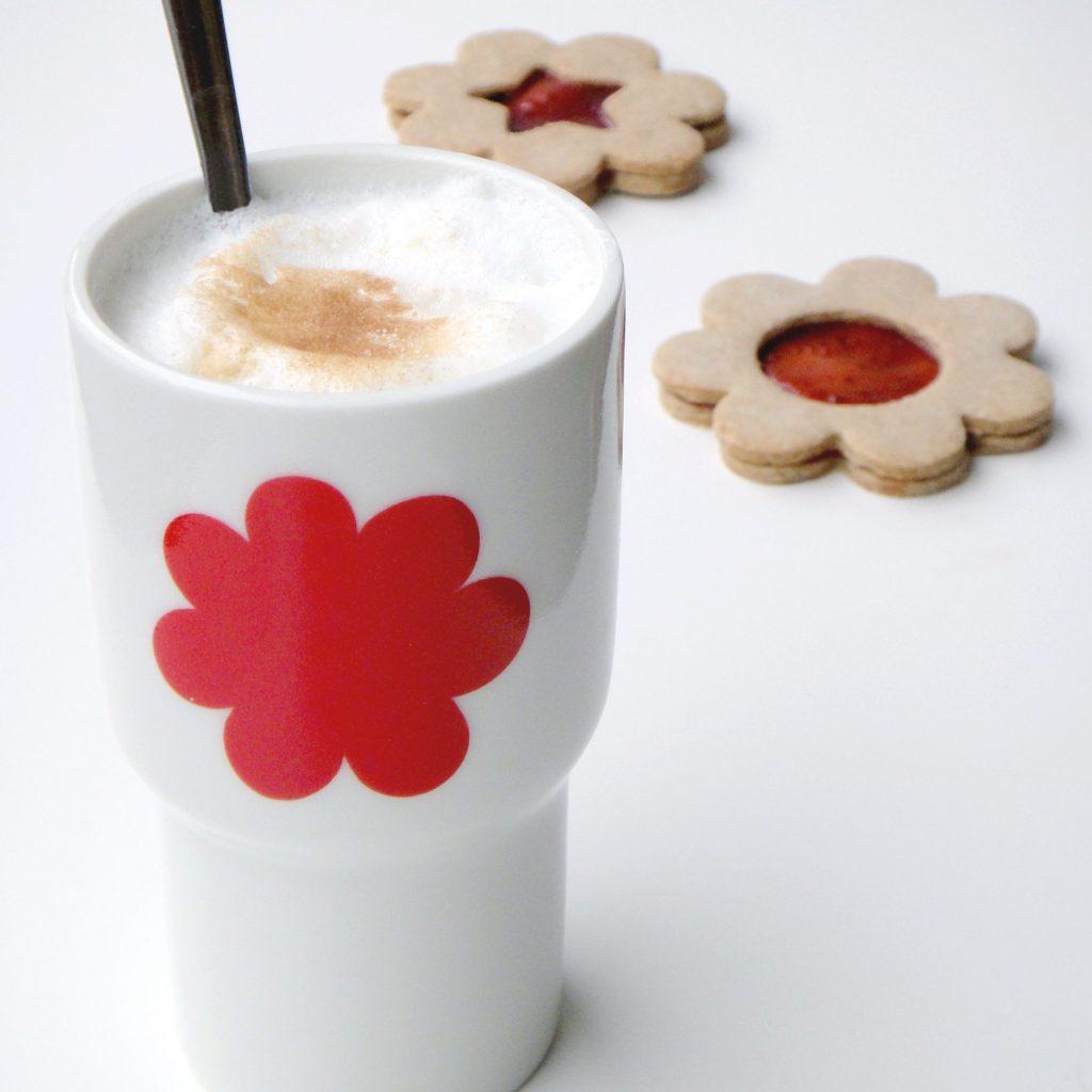 """weißer Porzellan-Becher der Serie """"tuvalu"""" mit dem roten Dekor """"Blume"""", dahinter liegen 2 Kekse"""