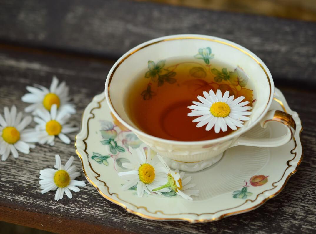 Teetasse mit Kamillentee und Blüten