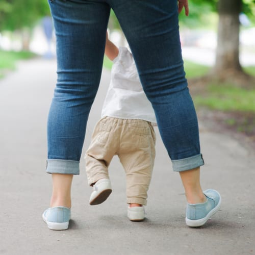 Baby walking holding onto Mommy's hands, seen from behind