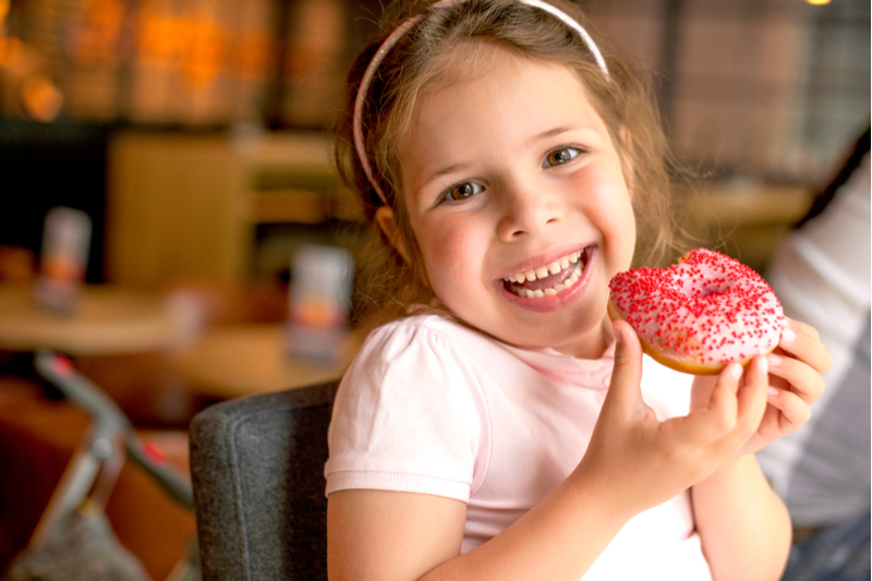 Smiling girl holds donut to illustrate risk of childhood obesity leading to type 2 diabetes