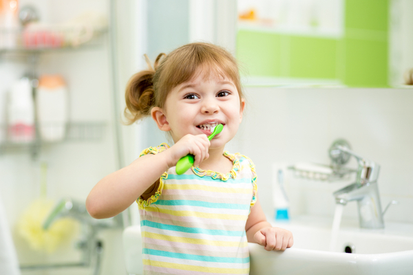 smiling blond girl brushes teeth