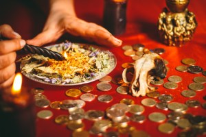 a witch holds a ritual for money burning a black candle