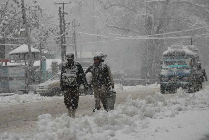 Snow bound: Paramilitary men walking in Srinagar