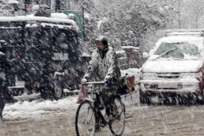 Bounded Ride: A man riding on bicycle amid snowfall in Srinagar
