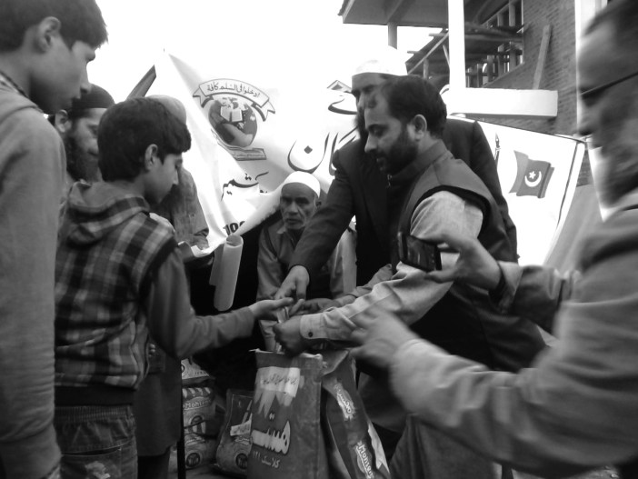 Jama'at-e-Islami Central officials distributing food items during 2014 September floods.