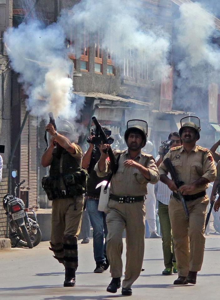 Policemen firing pepper guns towards civilian protesters (not in picture) during clashes in Srinagar.