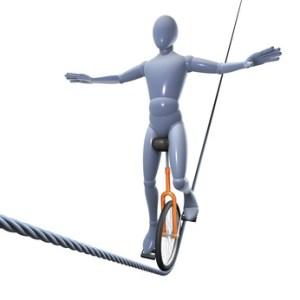 Figur auf Einrad balancierend auf Drahtseil