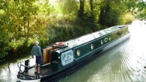 A narrowboat on the canal, a customer on a canal holiday