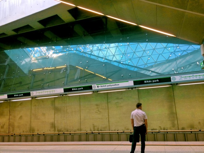 bikas park metro stop underground M4 Budapest public transport public sphere architecture station design tunnel subway waiting man platform reflection glass mirror engrave