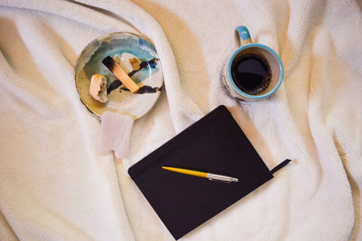photo of self care in action with journal, coffee cup and other items on a blanket