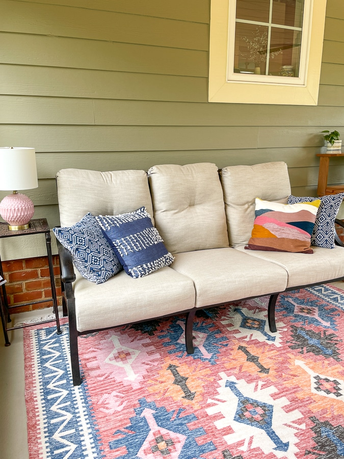 screened in porch with sofa and coral rug from west elm