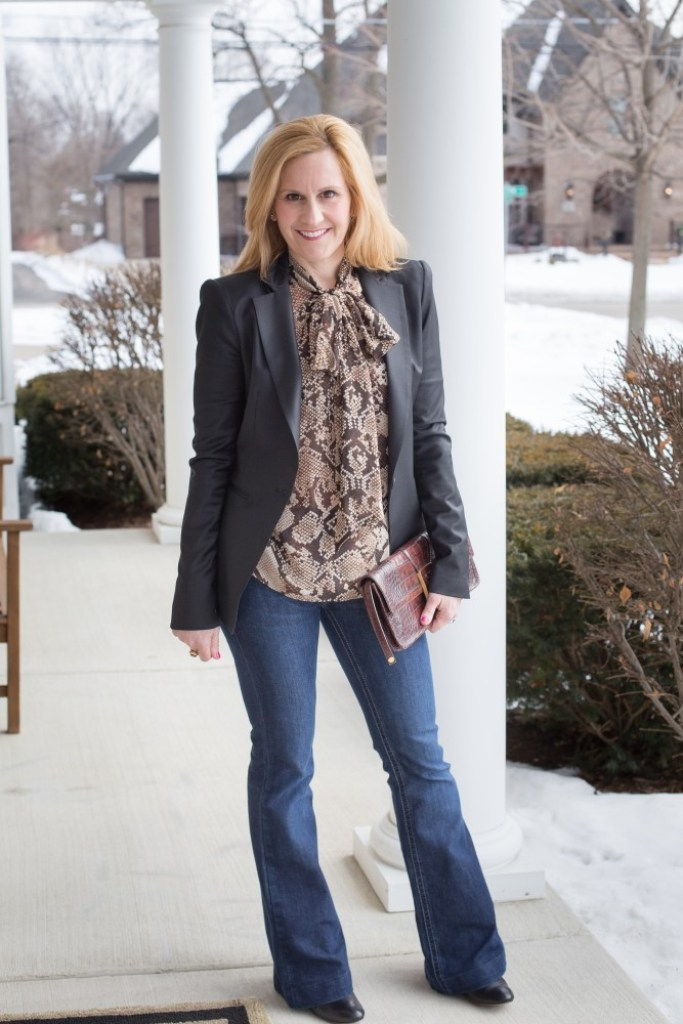 A smart business casual look featuring dark flared jeans and a snakeskin blouse.