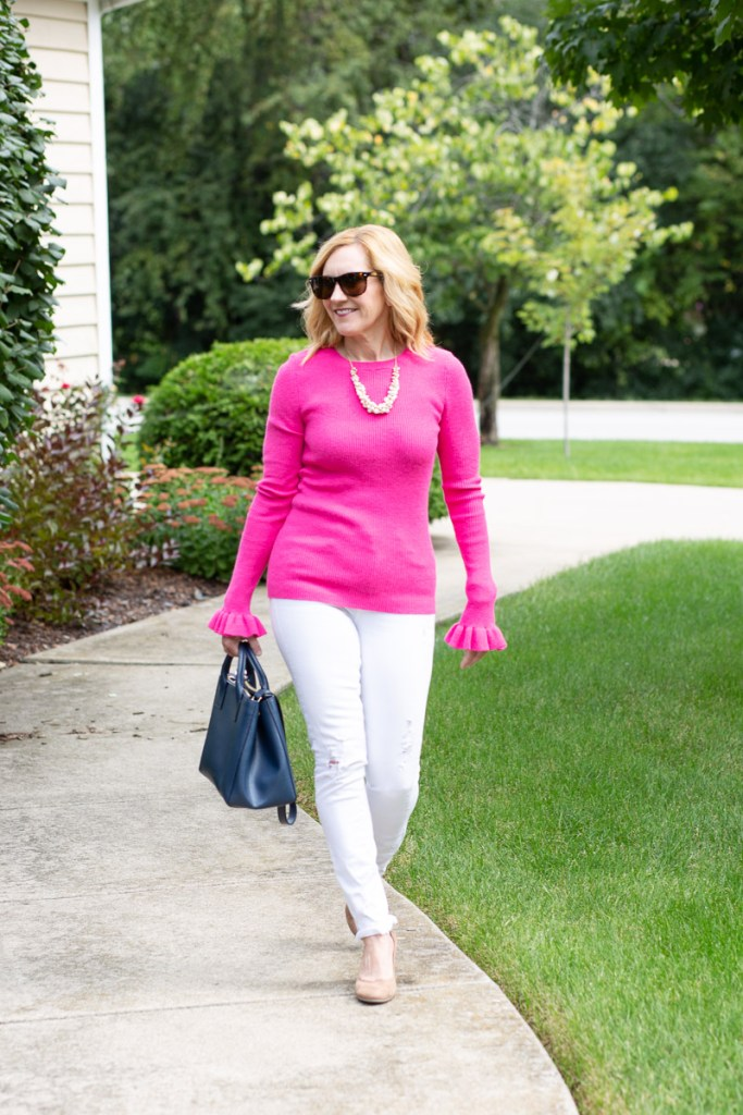 Styling white jeans with a bold pink knit top.